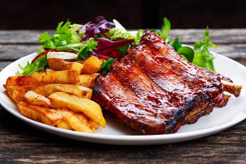 Reforço de carne de porco Roasted, Fried Potato na placa branca com vegetais fotos de stock