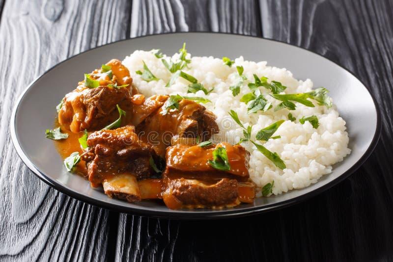 Reforços curtos lentamente cozinhados em um molho picante com close-up do prato lateral do arroz em uma placa horizontal fotografia de stock royalty free