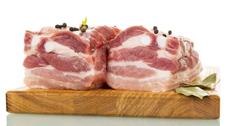 Reforços de carne de porco crus com as especiarias isoladas no branco fotografia de stock royalty free