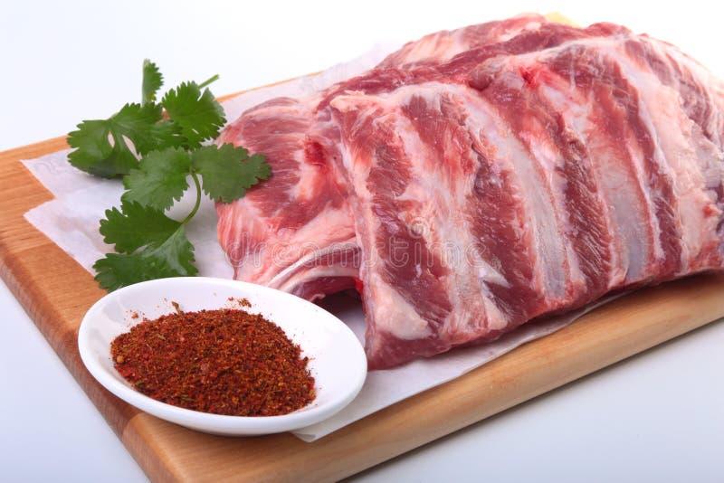 Reforços de carne de porco crus com ervas e especiarias na placa de madeira Apronte cozinhando imagem de stock royalty free