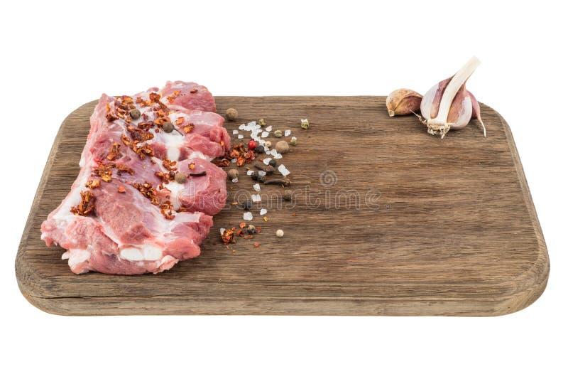 Reforços de carne de porco crus com pimentas de pimentão na placa de corte isolada no wh imagens de stock