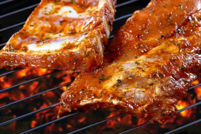 Reforços de carne de porco crus na grade imagem de stock