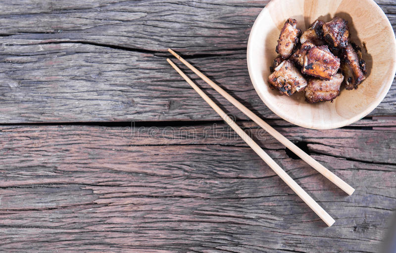 Reforços de carne de porco fritados, alho, alimento tailandês na tabela de madeira imagem de stock royalty free