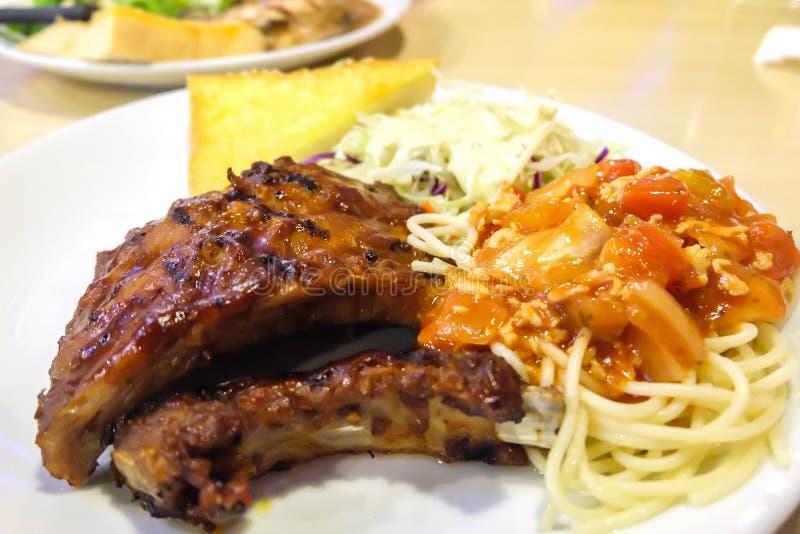 Reforços de carne de porco grelhados com espaguetes da salada e pão da manteiga imagens de stock