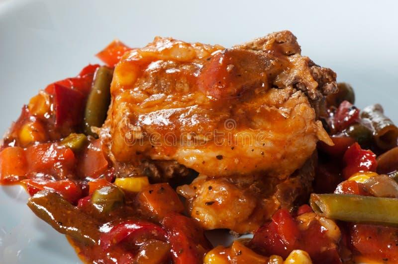 Reforços de carne de porco com milho, pimenta, tomates e os feijões verdes fotos de stock royalty free