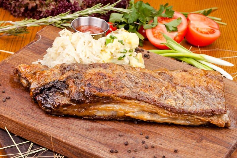 Reforços de carne de porco com salada de batata na placa de corte de madeira fotos de stock royalty free