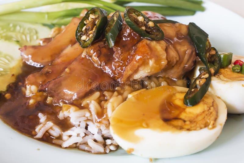 Reforços de carne de porco do arroz cobertos com molho tailandês delicioso do alimento foto de stock