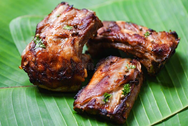 Reforços de carne de porco do BBQ grelhados com as especiarias das ervas servidas na folha da banana - a entrecosto de porco de c imagens de stock royalty free