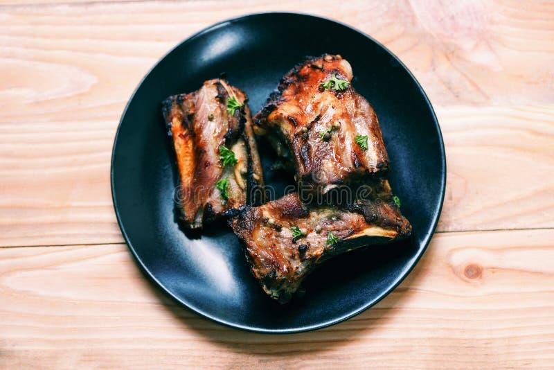 Reforços de carne de porco do BBQ grelhados com ervas e especiarias na placa servida na tabela de madeira - a entrecosto de porco fotos de stock