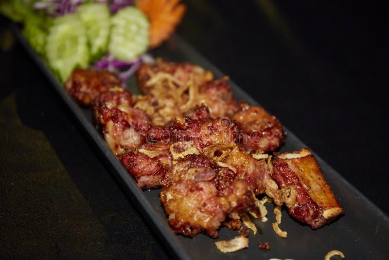Reforços de carne de porco fritados com alho fritado fotografia de stock
