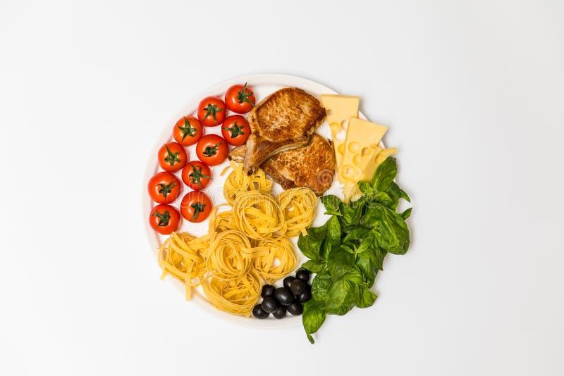 Reforços de carne de porco fritados com espaguetes, tomates de cereja, manjericão, azeitonas e queijo fotos de stock
