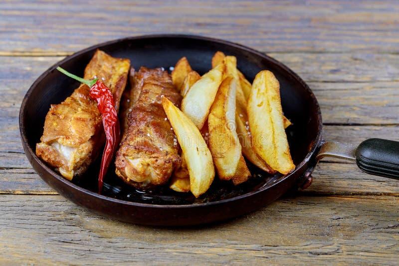 Reforços de carne de porco fritados na frigideira, e com batatas perto acima foto de stock royalty free