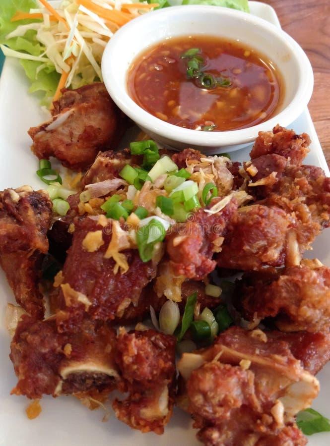 Reforços de carne de porco fritados no prato, alimento tailandês, Tailândia imagens de stock
