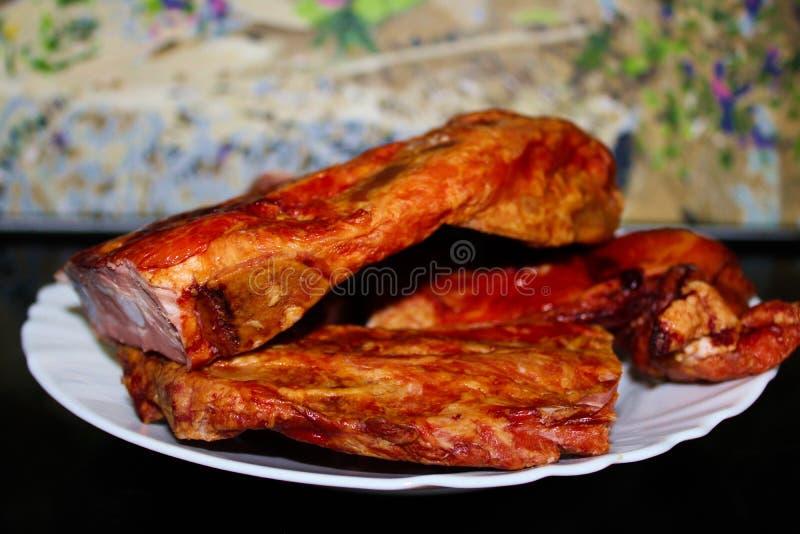 Reforços de carne de porco fumados em uma bandeja branca imagem de stock