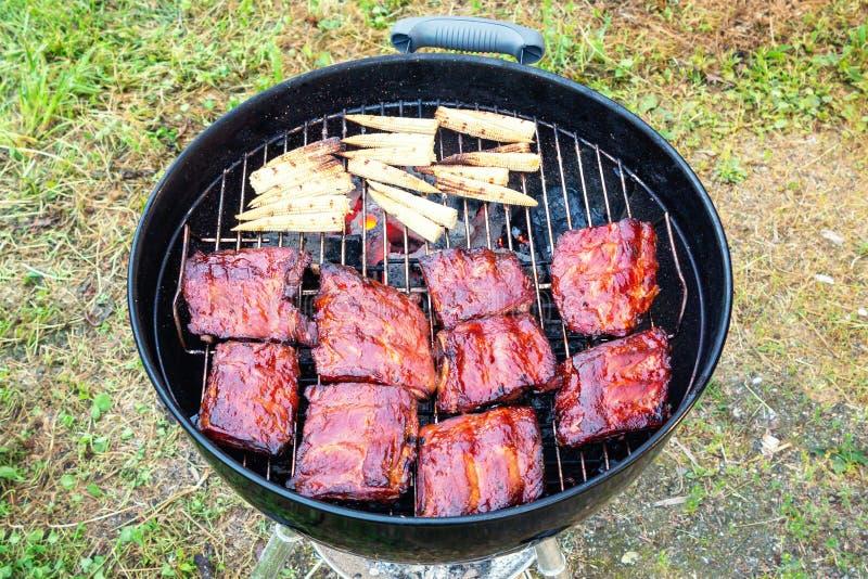 Reforços de carne de porco grelhados e mini milho na grade redonda do BBQ fotos de stock royalty free