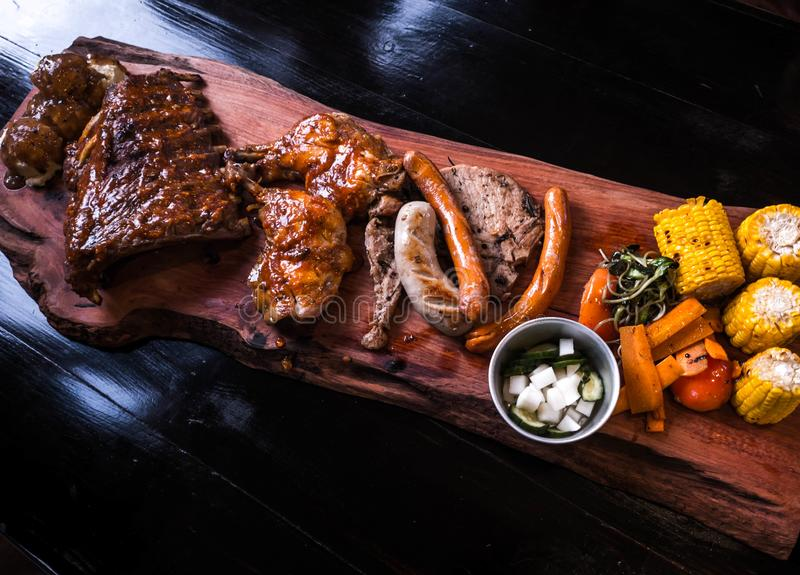Reforços de carne de porco, salsichas, costeletas de carne de porco e galinha grelhada em uma bandeja de madeira imagens de stock