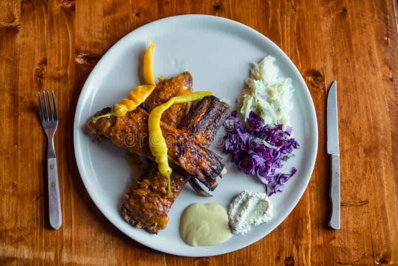 Reforços deliciosos do BBQ com salada e papel na placa branca fotografia de stock