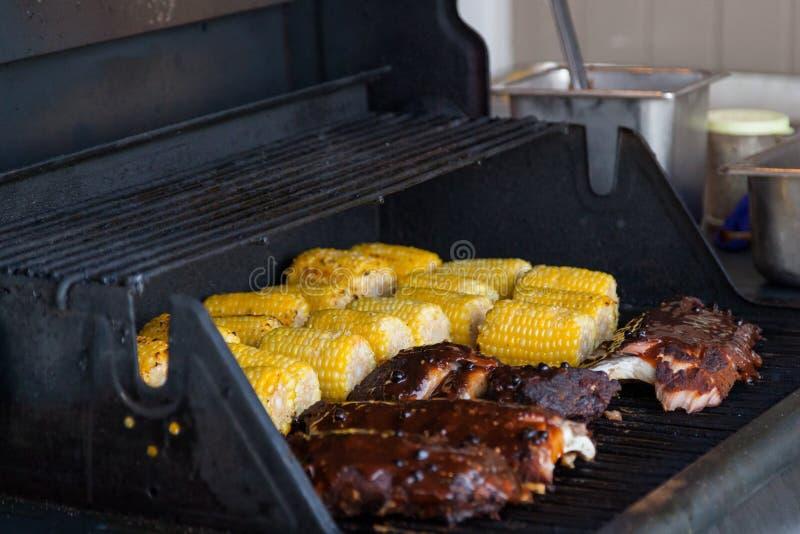 Reforços e milho no BBQ foto de stock