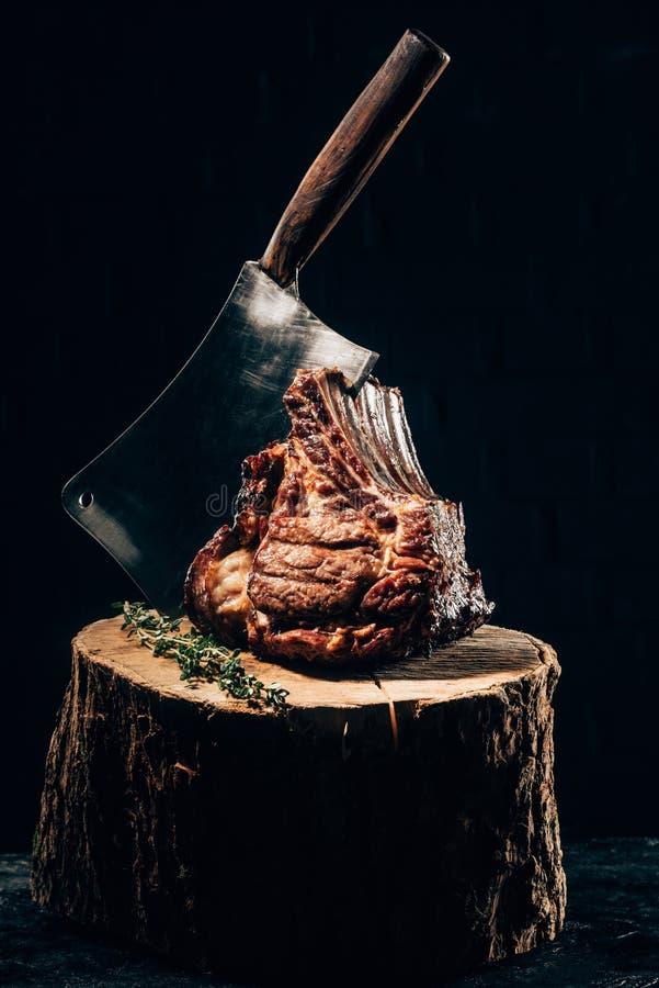 Reforços grelhados deliciosos com faca e alecrins da carne no coto de madeira fotos de stock royalty free