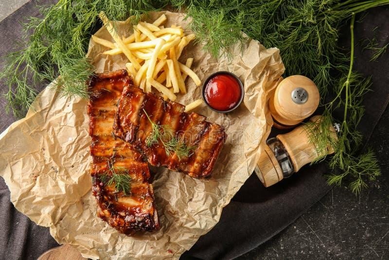 Reforços grelhados deliciosos com molho e batatas fritas no pergaminho imagens de stock