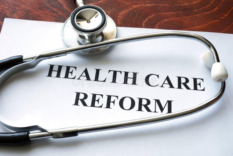 Reforma dos cuidados médicos das palavras escrita em um papel fotografia de stock