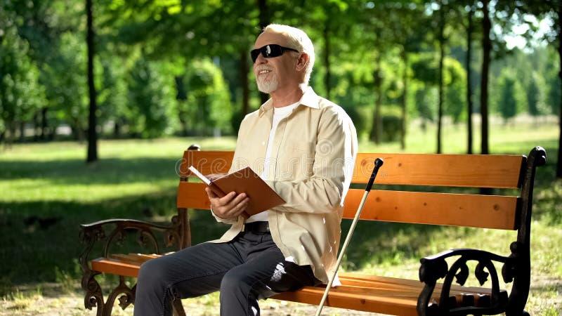 Reformado cego feliz lendo uma história engraçada no livro braille, desfrutando do descanso no parque foto de stock