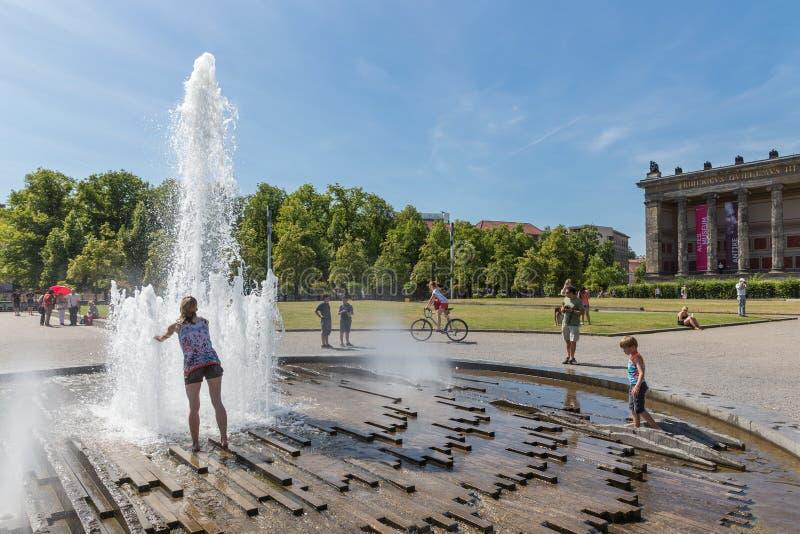 Refresco que busca de la gente desconocida en un día de verano caliente en la plaza cerca de los Dom del berlinés imagen de archivo