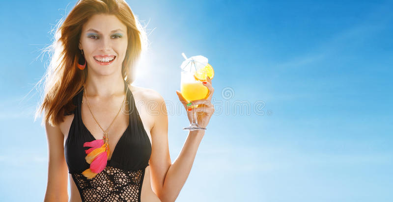 Refresh beverage. Portrait of happy smiling girl wearing swimsuit with tropical cocktail in her hand on blue background royalty free stock photos