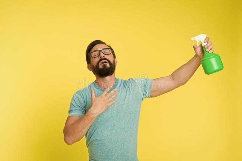 Refresh concept. Bearded man with eyeglasses refresh sprinkling water. Man refresh with spray bottle yellow background. Time to refresh yourself. Heat season royalty free stock photography