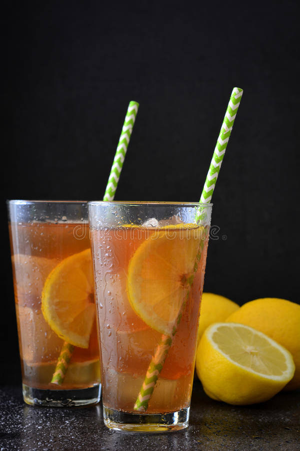 Refresh Ice tea with lemon. Black stone background stock photography