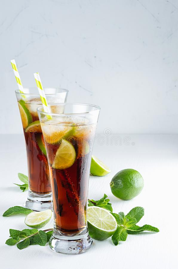 Refreshing alcohol beverage cuba libre with cola, ice, mint, lime, straw in two wet long glasses in modern white kitchen interior, stock photo
