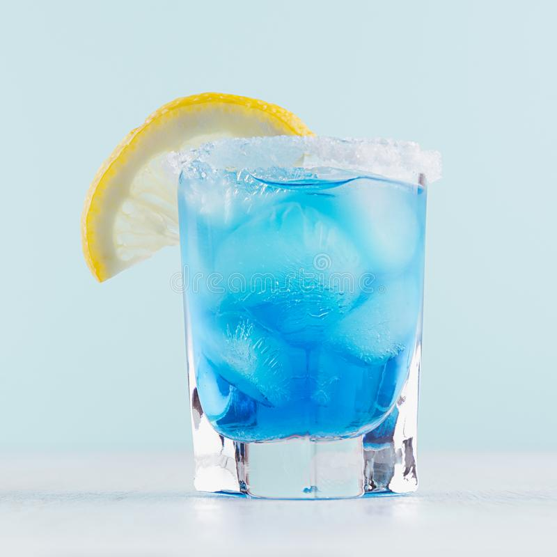 Free Refreshing Alcohol Drink Blue Hawaii In Misted Rich Shot Glass With Ice Cubes, Lemon Slice, Salt Rim In Modern Pastel Mint Color. Royalty Free Stock Photo - 150304045