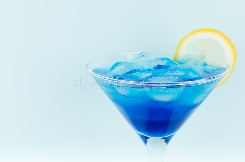 Refreshing alcohol drink blue Hawaii in misted rich wine glass with ice cubes, lemon slice in modern pastel mint background. royalty free stock photos