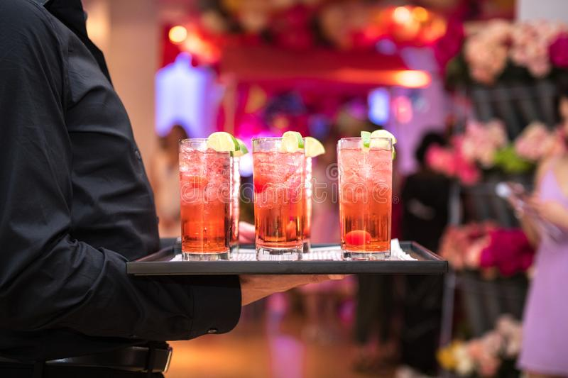 Refreshing alcohol red cocktails with ice and lemon on waiter plate on evening event party. stock photo