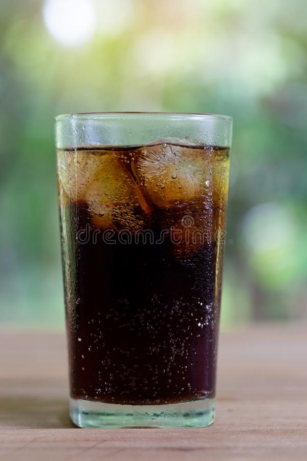 Refreshing black soda soft drinks or cola with ice in a clear tall glass with nature background. Refreshing black soda soft drinks or cola with ice in a clear royalty free stock photography