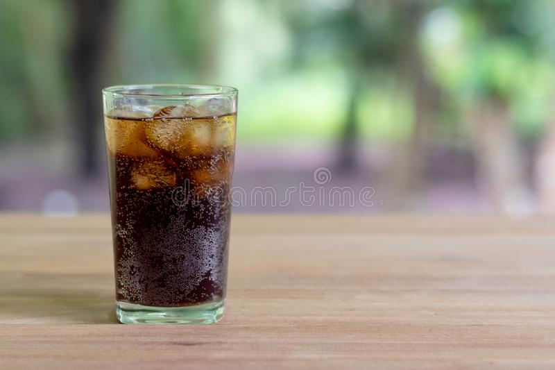 Refreshing black soda soft drinks or cola with ice in a clear tall glass with nature background. Refreshing black soda soft drinks or cola with ice in a clear stock photo