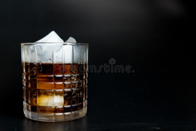 Refreshing black soda soft drinks with ice in a clear glass. On black background stock images