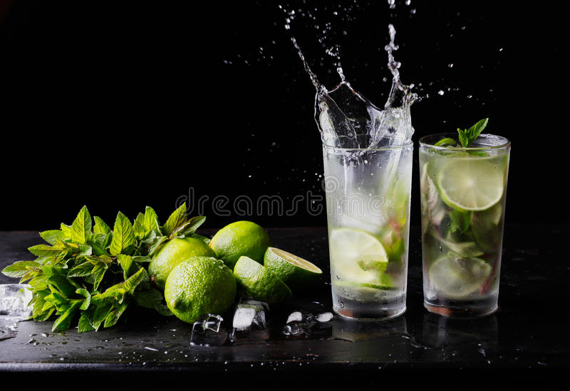 Refreshing cocktail mojito lemonade with splashes, lime and mint on the table. Black background. Close-up. stock images