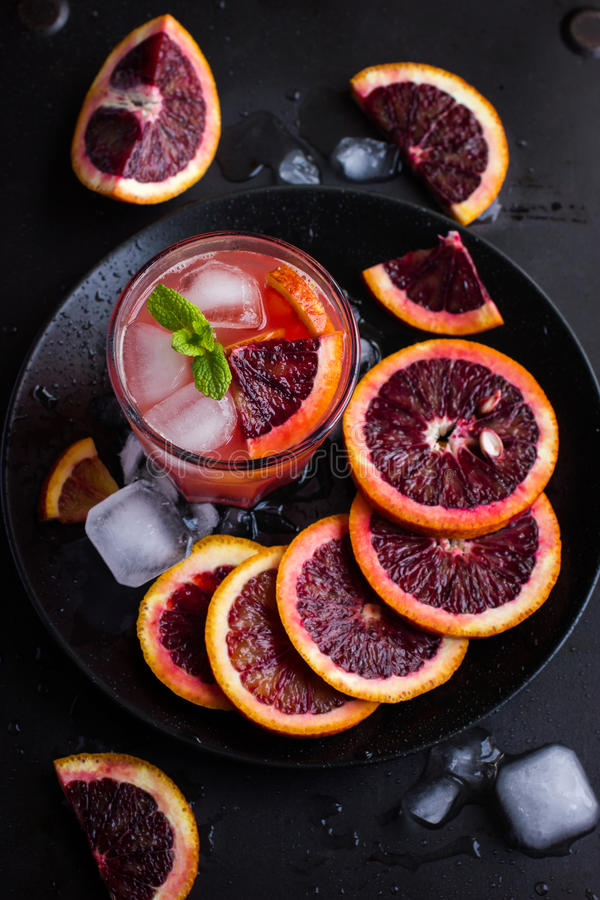 Refreshing cocktail with red blood orange, ice and mint royalty free stock image