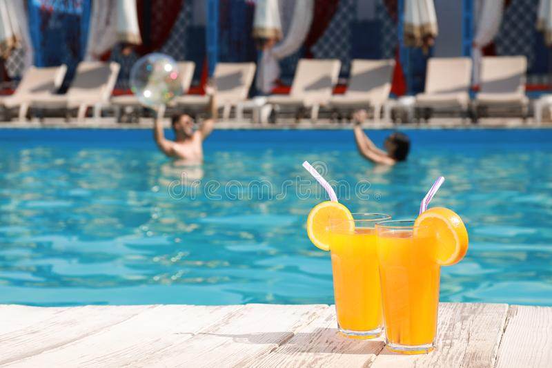 Refreshing cocktails and young couple in swimming pool on background stock photo