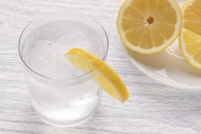 Refreshing cold water with lemon. With ice. Ready to eat. Next is a knife after cutting fruit. Misted glass royalty free stock images