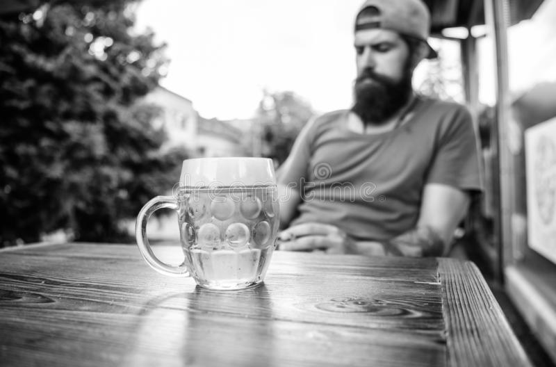 Refreshing with crisp finish. Chilled beer mug on cafe table. Brutal man relaxing with alcoholic drink in beer. Restaurant. Bearded man drinking beer in bar royalty free stock image