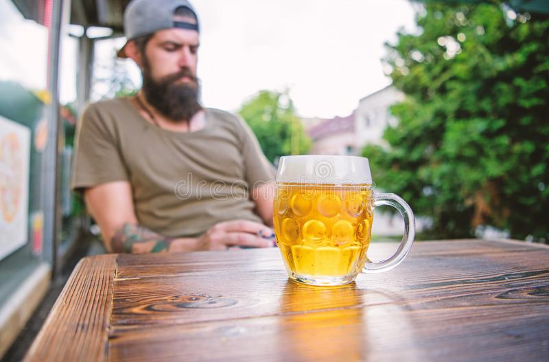Refreshing with crisp finish. Chilled beer mug on cafe table. Brutal man relaxing with alcoholic drink in beer. Restaurant. Bearded man drinking beer in bar stock photography