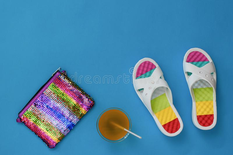 Refreshing drink, bag and flip flops on a blue background. The concept of summer vacation. Flat lay. royalty free stock image