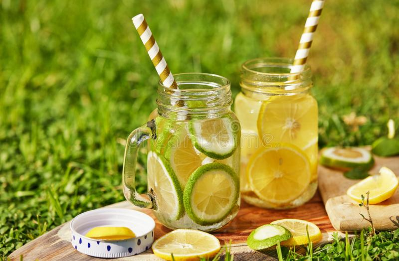 Refreshing drink with lemon and lime in special jars with straws on a wooden stand, shot in the morning on the green grass. stock image