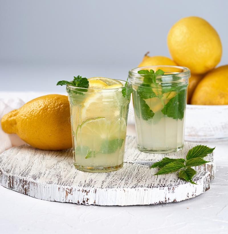 Refreshing drink lemonade with lemons, mint leaves, lime in a glass. Summer refreshing drink lemonade with lemons, mint leaves, lime in a glass , next to the royalty free stock image