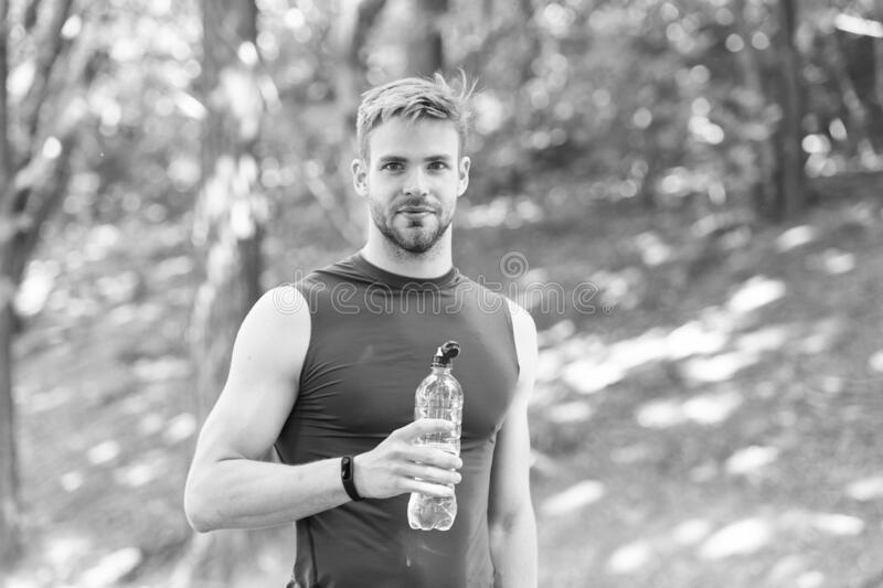 Refreshing drink. Man athletic sportsman hold bottle water. Athlete drink water after training in park. Vitamins and royalty free stock photography