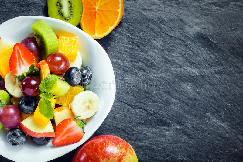 Refreshing fresh tropical fruit salad. Refreshing bowl of fresh tropical fruit salad with ingredients on a textured slate kitchen counter with copyspace royalty free stock images