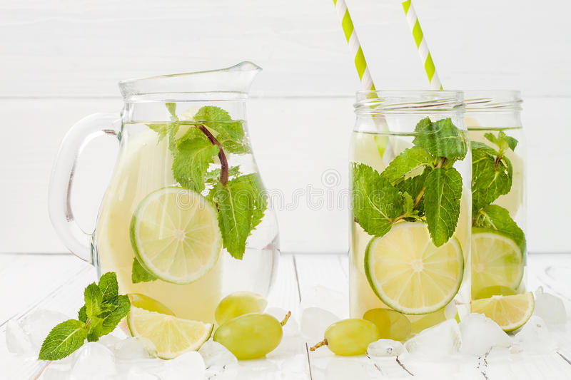 Refreshing homemade lime and mint cocktail over old vintage wooden table. Detox fruit infused flavored water. Clean eating stock photo