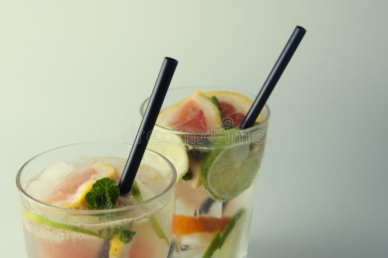 Refreshing iced mint drink with lemon and ice cubes, a drink for hot summer days selective focus, toned image. Iced mint drink with lemon and ice cubes, a drink stock image